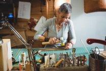 Зрелая ремесленница молотит кожей в интерьере мастерской — стоковое фото