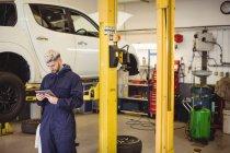 Mecânico usando tablet digital na garagem de reparação — Fotografia de Stock