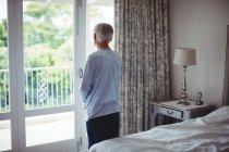Homme âgé regardant par la fenêtre dans la chambre à coucher à la maison — Photo de stock