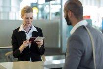 Pendolari in piedi al banco mentre controllano il passaporto al terminal dell'aeroporto — Foto stock