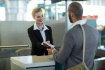 Passaporto dell'addetto al check-in della compagnia aerea per i pendolari al banco del terminal aeroportuale — Foto stock