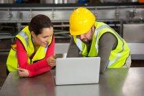 Чоловічі і жіночі робітників, використовуючи ноутбук у заводу — стокове фото