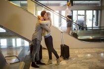Pareja alegre abrazándose en la terminal del aeropuerto - foto de stock