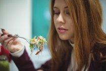 Крупный план красивой женщины, которая ест салат — стоковое фото