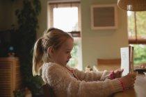 Chica rubia sentada en la mesa y lectura en el hogar - foto de stock