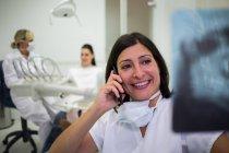 Dentista checando relatório de raio-x enquanto fala no telefone celular na clínica estética — Fotografia de Stock