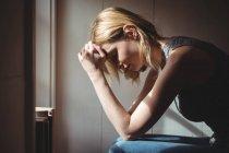 Напряженная женщина сидит с рукой на лбу дома — стоковое фото