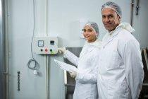 Portrait de techniciens tenant un dossier sur presse-papiers à l'usine — Photo de stock