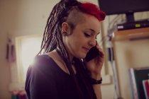 Parrucchiere femminile che parla sul telefono cellulare nel negozio di dreadlocks — Foto stock