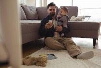 Père tenant son bébé tout en utilisant un téléphone portable à la maison — Photo de stock