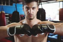 Portrait of boxer performing boxing stance in fitness studio — Stock Photo