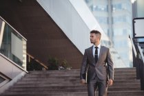 Empresário com um diário descendo escadas no escritório — Fotografia de Stock