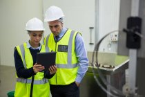 Two technicians discussing over digital tablet at meat factory — Stock Photo