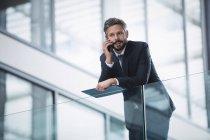 Uomo d'affari che parla sul cellulare all'interno di un edificio per uffici — Foto stock