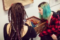 Female shop owner interacting with a customer in dreadlocks shop — Stock Photo