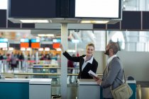 Airline check-in attendant showing direction to commuter at check-in counter in airport terminal — Stock Photo