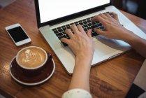 Las manos de la mujer de negocios utilizando el ordenador portátil en la mesa de café - foto de stock
