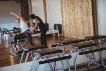 Coach helping woman while practicing pilates in fitness studio — Stock Photo