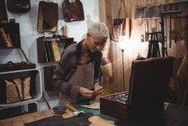 Ремесленница, работающая над куском кожи в мастерской — стоковое фото