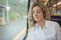 Mujer de negocios cansada durmiendo mientras viaja en tren - foto de stock