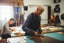Artisanat attentif coupant le cuir dans l'atelier — Photo de stock