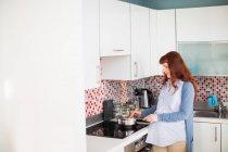Mulher grávida cozinhar alimentos na cozinha em casa — Fotografia de Stock