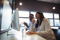 Empresário e um colega que trabalha por computador no escritório — Fotografia de Stock