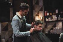 Клиент стрижет волосы бритвой в парикмахерской — стоковое фото