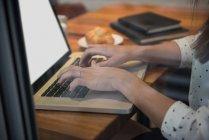 Las manos de la mujer de negocios utilizando el ordenador portátil en el café - foto de stock