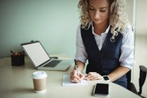 Businesswoman writing on notepad in office — Stock Photo
