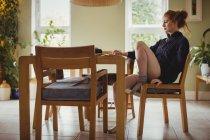 Beautiful woman using digital tablet at home — Stock Photo
