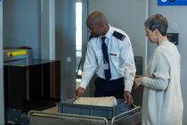 Flughafen-Security-Officer Überprüfung eine Tasche der Pendler im Flughafen-terminal — Stockfoto