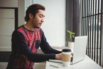 Homme utilisant un ordinateur portable tout en prenant un café dans un café — Photo de stock