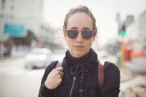 Ritratto di donna che indossa occhiali da sole in città — Foto stock