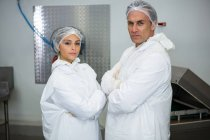 Carniceros de pie con los brazos cruzados en fábrica de carne - foto de stock