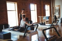 Coach assisting a woman while practicing pilates in fitness studio — Stock Photo