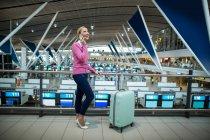 Navetteur féminin avec bagages parlant sur téléphone portable à l'aéroport — Photo de stock