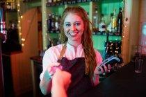 Клиент делает оплату с помощью кредитной карты на стойке в баре — стоковое фото