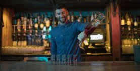 Bartender pouring alcoholic drink in shot glasses at bar — Stock Photo