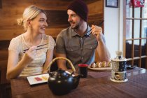 Smiling couple having sushi in restaurant — Stock Photo