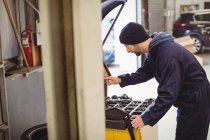 Mecânico usando dispositivo de diagnóstico eletrônico na garagem de reparação — Fotografia de Stock