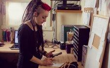 Cabeleireiro feminino usando telefone celular e fazendo anotações na loja dreadlocks — Fotografia de Stock