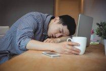 Un dirigeant d'entreprise dort à son bureau — Photo de stock