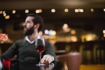 Man sitting with glass of wine in bar — Stock Photo