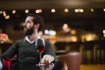 Homme assis avec un verre de vin au bar — Photo de stock