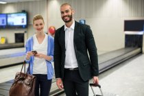 Portrait of couple standing with luggage at waiting area in airport — Stock Photo