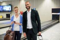 Ritratto di coppia in piedi con bagagli in sala d'attesa in aeroporto — Foto stock