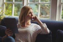 Femme réfléchie assise sur un canapé avec table numérique dans le salon à la maison — Photo de stock