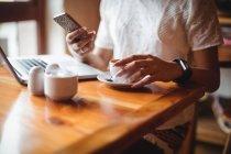A meio da seção da mulher usando telefone celular enquanto toma uma xícara de café no café — Fotografia de Stock