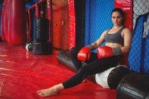 Retrato de boxer feminino sentado no saco de pancadas no estúdio de fitness — Fotografia de Stock